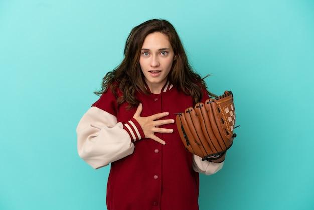 青い背景に分離された野球をしている若い白人女性は、右を見ながら驚いてショックを受けました