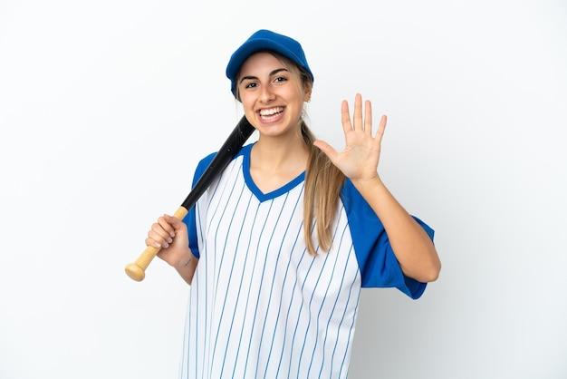 Молодая кавказская женщина играет в бейсбол на белом фоне, считая пять пальцами
