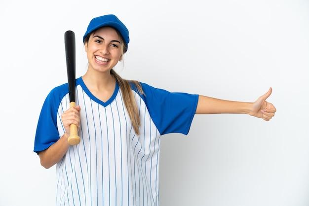 Молодая кавказская женщина играет в бейсбол, изолированную на белом фоне, показывает палец вверх жестом