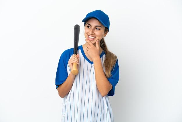 Молодая кавказская женщина играет в бейсбол на белом фоне, глядя в сторону и улыбается