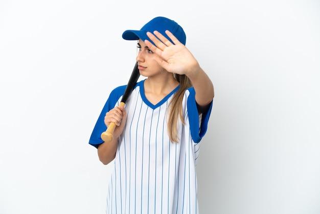 Молодая кавказская женщина играет в бейсбол на белом фоне, делая жест стоп и разочарована