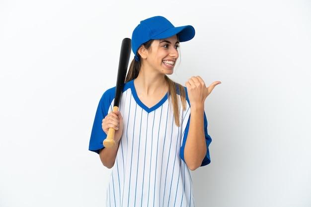 Молодая кавказская женщина играет в бейсбол на белом фоне, указывая в сторону, чтобы представить продукт