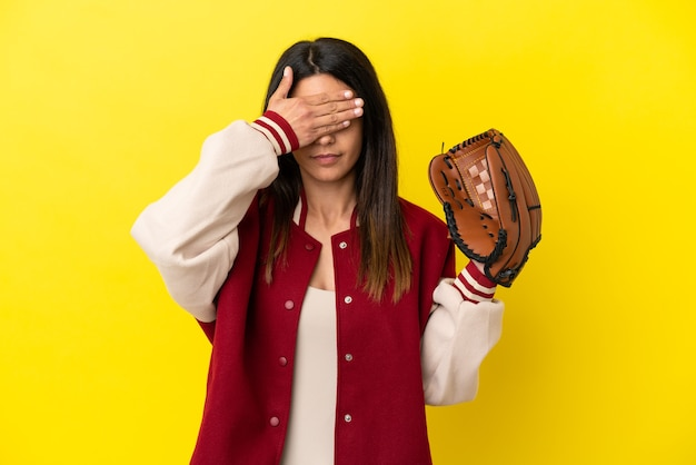 손으로 눈을 덮고 노란색 배경에 고립 야구를 하는 젊은 백인 여자. 뭔가 보고 싶지 않아