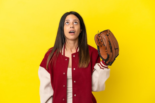 Молодая кавказская женщина играет в бейсбол на желтом фоне смотрит вверх и с удивленным выражением лица