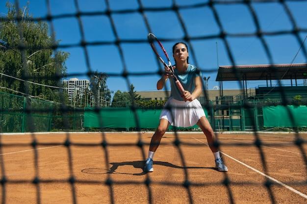 야외 테니스 코트에서 테니스를 치는 백인 젊은 여성