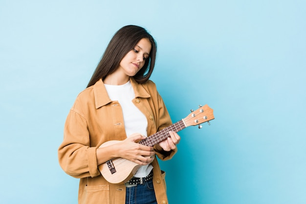 Young caucasian woman playing ukelele isolated on a blue wall