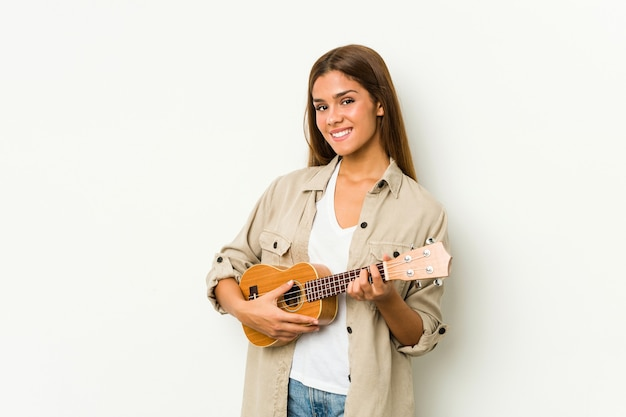 Young caucasian woman playing ukelele isolated
