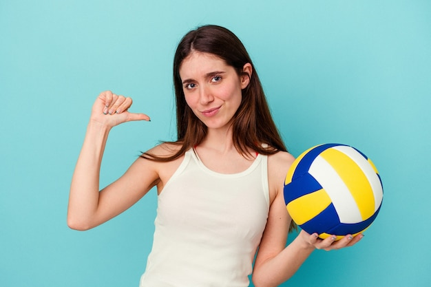 Young caucasian woman playing volleyball isolated on blue background feels proud and self confident, example to follow.