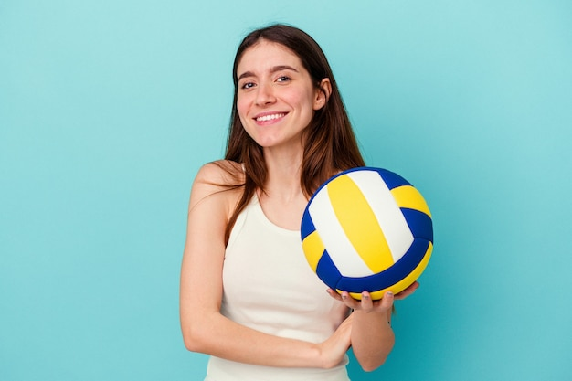 Young caucasian woman playing volleyball isolated on blue background laughing and having fun.
