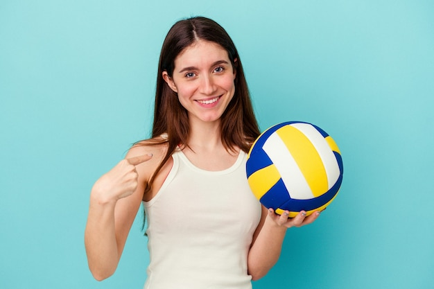 Young caucasian woman playing volleyball isolated on blue background pointing with finger at you as if inviting come closer.