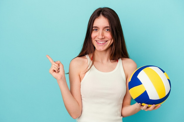 Young caucasian woman playing volleyball isolated on blue background smiling and pointing aside, showing something at blank space.