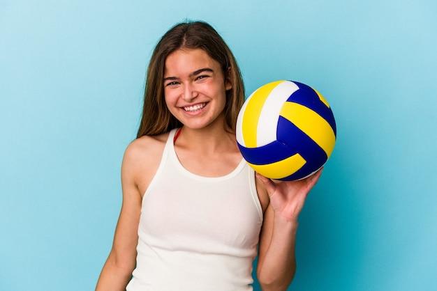 Молодая кавказская женщина играет в волейбол на синем фоне, счастливая, улыбающаяся и веселая.