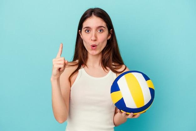 いくつかの素晴らしいアイデア、創造性の概念を持っている青い背景に分離されたバレーボールをしている若い白人女性。