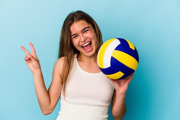 青い背景で隔離のバレーボールをしている若い白人女性は、指で平和のシンボルを示して楽しくてのんきです。