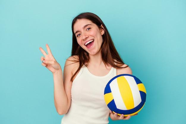 青の背景に分離されたバレーボールをしている若い白人女性は、指で平和のシンボルを示して楽しくてのんきです。