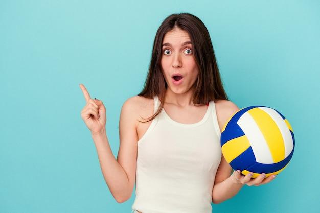 側面を指している青い背景で隔離のバレーボールをしている若い白人女性