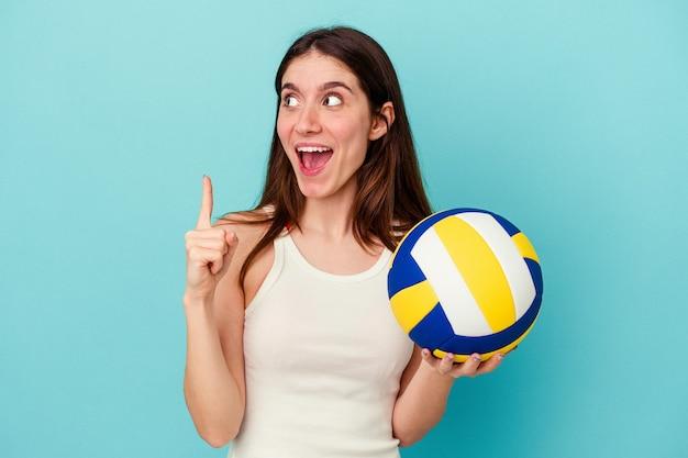 開いた口で逆さまを指している青い背景に分離されたバレーボールをしている若い白人女性。