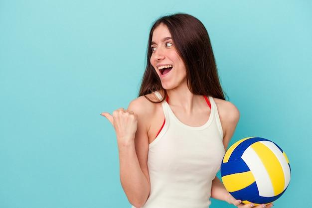 離れて親指の指で青い背景のポイントに分離されたバレーボールをしている若い白人女性は、笑ってのんき。