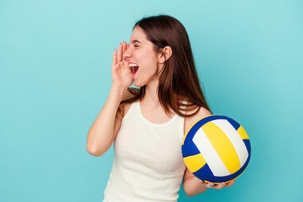 開いた口の近くで叫び、手のひらを保持している青い背景で隔離のバレーボールをしている若い白人女性。