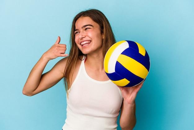 Молодая кавказская женщина играет в волейбол, изолированную на синем фоне, показывая жест мобильного телефона пальцами.