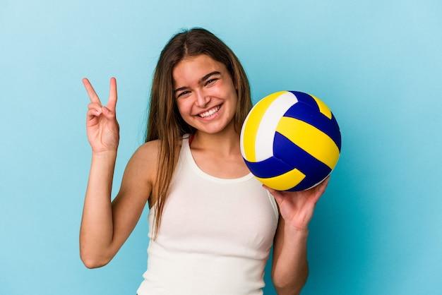 Молодая кавказская женщина играет в волейбол, изолированную на синем фоне, показывая пальцами номер два.