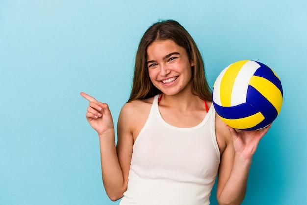 Молодая кавказская женщина играет в волейбол на синем фоне, улыбаясь и указывая в сторону, показывая что-то на пустом месте.