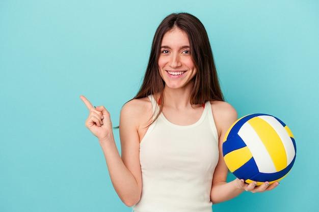 青い背景に分離されたバレーボールをしている若い白人女性が笑顔で脇を指して、空白のスペースで何かを示しています。