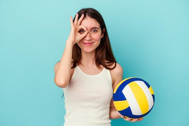 青い壁に隔離されたバレーボールをしている若い白人女性は、目の上で大丈夫なジェスチャーを維持して興奮しました。
