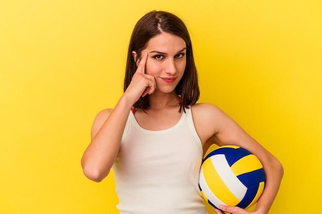 黄色の背景で隔離されたバレーボールをしている若い白人女性は、指で寺院を指して、考えて、タスクに焦点を当てた。
