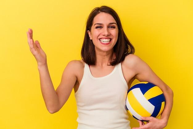 黄色の背景に分離されたバレーボールをしている若い白人女性は、嬉しい驚きを受け取り、興奮し、手を上げます。