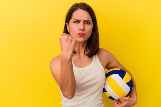 カメラに拳、攻撃的な表情を示す黄色の背景に分離されたバレーボールをしている若い白人女性。