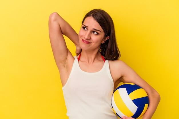頭の後ろに触れて、考えて、選択をする黄色の背景に分離されたバレーボールをしている若い白人女性。