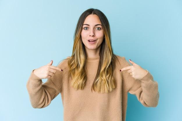 若い白人女性は指で下向き、前向きな気持ち。