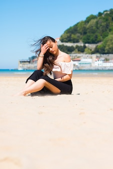 Молодая кавказская женщина позирует на пляже
