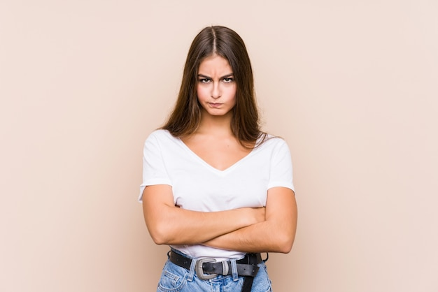 Young caucasian woman posing frowning face in displeasure, keeps arms folded.