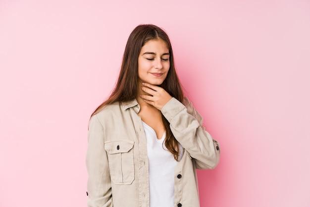 Молодая кавказская женщина позирует у розовой стены и страдает от боли в горле из-за вируса или инфекции.