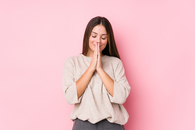 Young caucasian woman posing isolated holding hands in pray near mouth, feels confident.