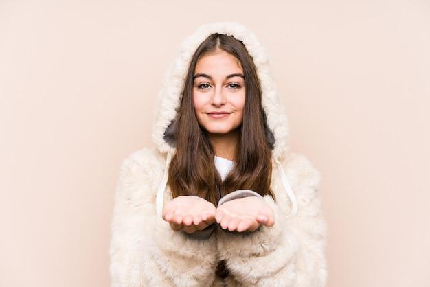 Молодая кавказская женщина позирует изолированно, держа что-то ладонями, предлагая что-то