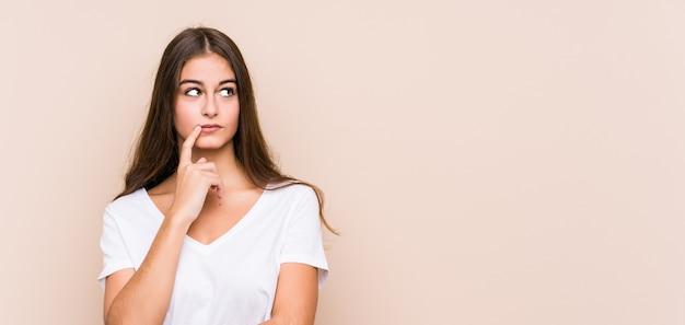 젊은 백인 여자는 의심스럽고 회의적인 표정으로 옆으로 고립 된 찾고 포즈.