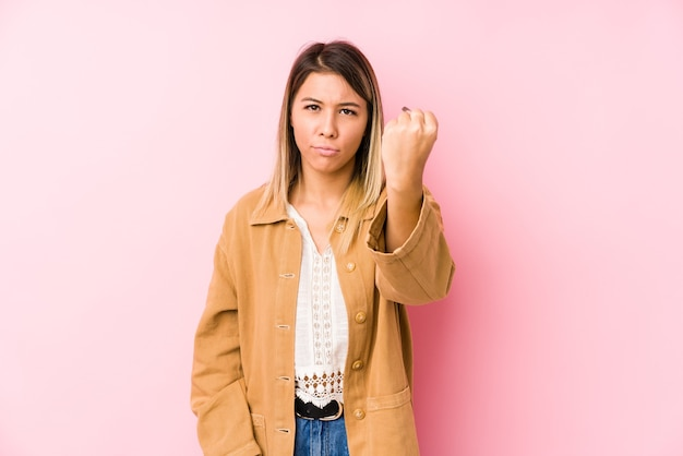 Young caucasian woman posing isolated showing fist , aggressive facial expression.