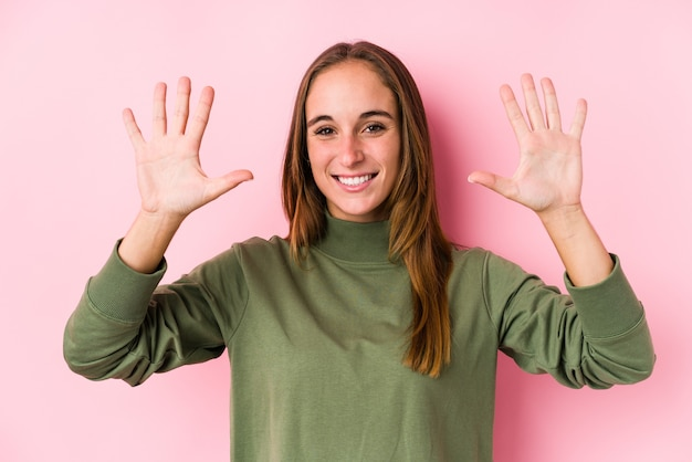 Young caucasian woman posing isolated  showing number ten with hands.