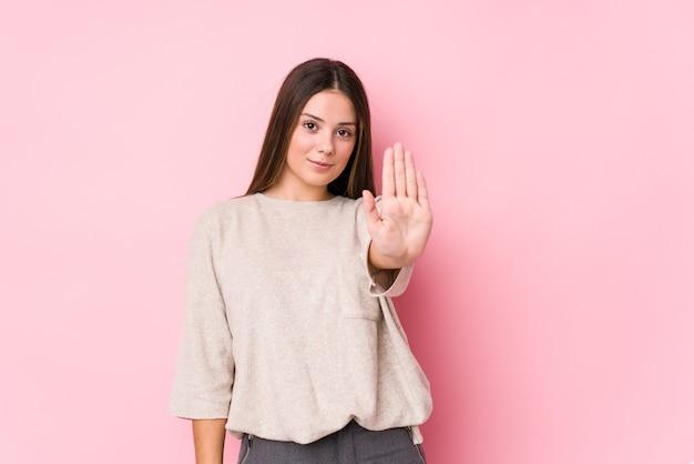Молодая кавказская женщина позирует изолированным стоя с протянутой рукой, показывая знак остановки, предотвращая вас.