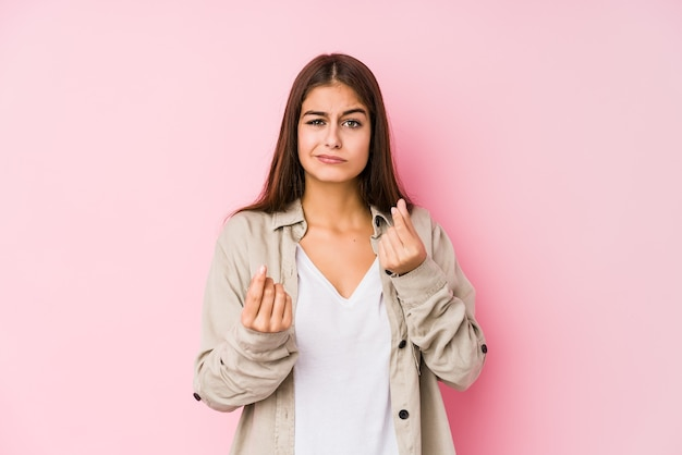 Young caucasian woman posing on pink showing that she has no money.