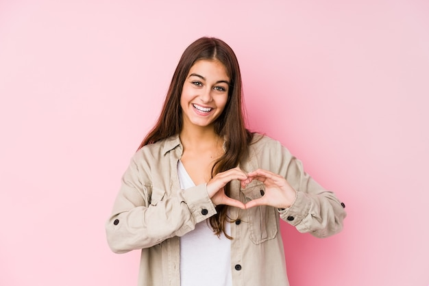 Young caucasian woman posing in a pink smiling and showing a heart shape with hands.