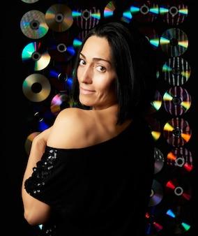 Young caucasian woman posing on shiny flickering dark