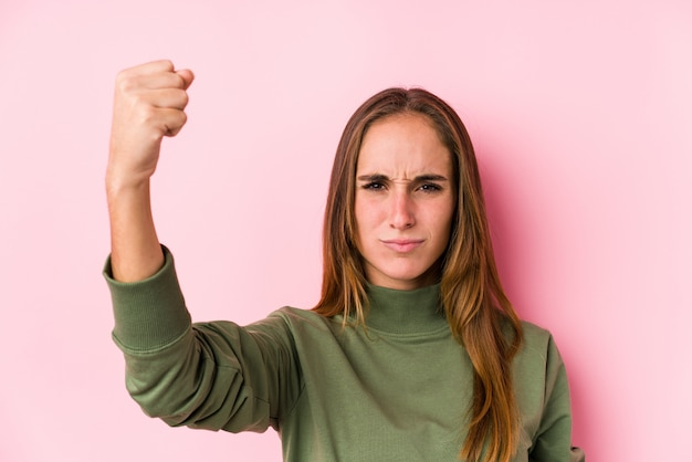 Young caucasian woman posing showing fist to camera, aggressive facial expression.