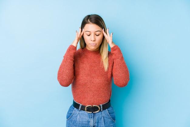 Young caucasian woman posing touching temples and having headache.