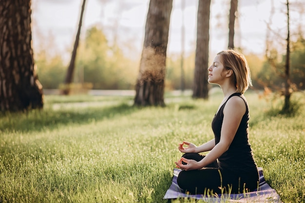 A young caucasian woman practices breathing yoga on an early sunny morning in the woods among the trees soft selective focus.