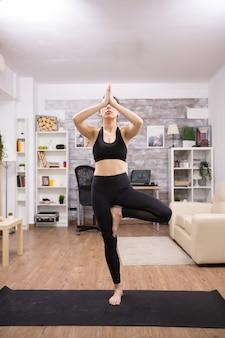 Young caucasian woman practicing tree yoga pose wearing black sportwear in home.