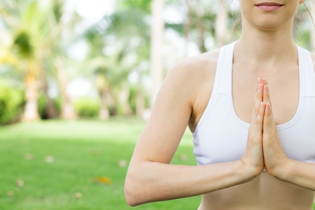 Young caucasian woman practicing yoga outdoors